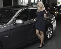 New car. Young blond smiling female holding car key in front of a new car stock photo
