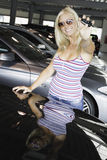 New car. Young blond smiling female holding car keys in front of line of new cars royalty free stock images