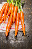 New carrots bunch on dark rustic wooden background Stock Photos