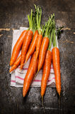 New carrots bunch on dark rustic wooden background Stock Images