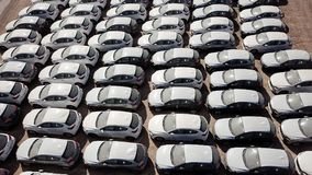 New cars covered in protective white sheets. Parked in a holding platform - Aerial image Stock Images