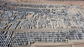 New cars covered in protective white sheets. Parked in a holding platform - Aerial image Royalty Free Stock Images