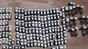 New cars covered in protective white sheets. Parked in a holding platform - Aerial image Stock Photos
