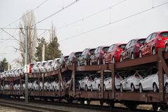 New cars demand leads to exports. Lots of cars being transported by rail Royalty Free Stock Photo