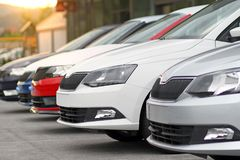New cars for sale parked in front of a car, motor dealer store, shop. Row of different modern european marques of new cars for retail sale on a motor dealers royalty free stock image