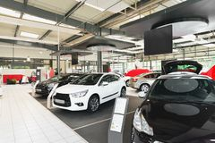 New cars in the sales area of a car dealership - building and ar. Chitecture of a car trade company royalty free stock image