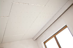 New ceiling installation. A new ceiling installation on a house under construction stock photography
