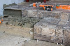 Repair of stone stairs,a new ceramic tile to lay on the stairs in the house, laying tiles on the stairs. A new ceramic tile to lay on the stairs in the house stock images