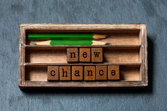 New chance phrase. Motivation and positive expectations concept. Vintage box, wooden cubes with old style letters, green Stock Images