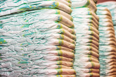 New children's diapers stacked in a piles in the child room Stock Photos