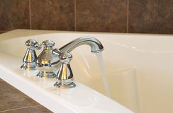 New Chrome Faucet in Master Bath Tub. Closeup horizontal photo of chrome faucet running water into soaking tub in master bathroom Royalty Free Stock Image