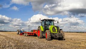 A Claas 630 tractor pulling a trailer to load vintage tractor. A new claas tractor pulling a low loader with a vintage old tractor Royalty Free Stock Images