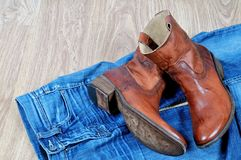 Brown cowboy boots on blue jeans. New classical leather brown cowboy boots on blue classical jeans stock images
