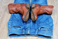 Brown cowboy boots on blue jeans. New classical leather brown cowboy boots on blue classical jeans stock photos