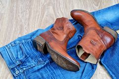 Brown cowboy boots on blue jeans. New classical leather brown cowboy boots on blue classical jeans royalty free stock image