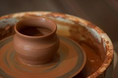 New clay cup on a potter`s wheel. Handwork. Red clay. royalty free stock images