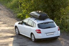 New clean white modern car with black roof luggage box container moving along empty asphalt road in bad condition by green trees a. Nd bushes on bright sunny day stock image