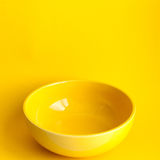 New clean yellow bowl. On yellow background. Frontal view Royalty Free Stock Photography