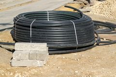 New coil of black electric cable or hank of plastic pipes for laying in a trench at the site of the road works royalty free stock images