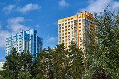 New colored apartment houses, clear blue sky, green trees in bottom.  Stock Images