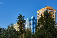 New colored apartment houses, clear blue sky, green trees in bottom.  Royalty Free Stock Photo