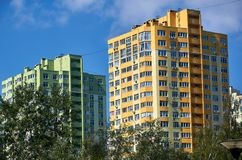 New colored apartment houses, clear blue sky, green trees in bottom.  Royalty Free Stock Photos