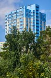 New colored apartment houses, clear blue sky, green trees in bottom.  Royalty Free Stock Images