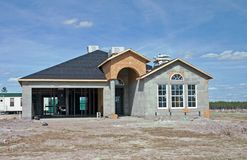 New concrete block home construction. Partially complete concrete block home with roof dried in Royalty Free Stock Image