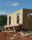 New Construction. Side wall of new home in the early phase of construction.  Plywood and dirt landscape are dominant in this image Royalty Free Stock Image