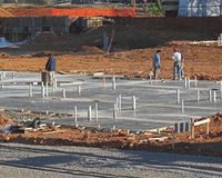 New Construction. Site, slab just completed with plumbing coming out of slab Royalty Free Stock Photography
