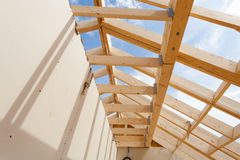 New construction home framing against blue sky, closeup of ceiling frame.with plasterboard wall.  Stock Photo