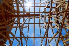 New construction home framing against blue sky, closeup of ceiling frame. Wood building on development New construction home framing against blue sky, closeup stock image