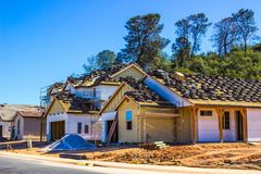 New Construction Homes. New Homes Under Construction With Roof Materials Waiting To Be Installed royalty free stock photos