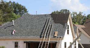 Roof Work on New House. A new construction house in the process of being constructed and having the roof and roofing system installed royalty free stock image