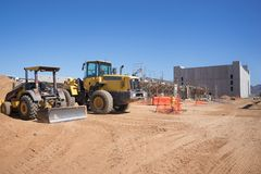 New Construction site with digger and earth mover in foreground. Stock Photo