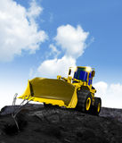 New construction truck. A clean new powerful yellow earth mover construction truck posed against a rocky background and blue sky Stock Photos