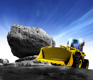 New construction truck. A clean new powerful yellow earth mover construction truck posed against a rocky background and blue sky Royalty Free Stock Images