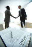 New contract. Image of business contract on background of two employees handshaking Royalty Free Stock Photography