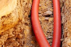 New corrugated PVC pipe for laying electric cable laid in the trench. Sandy soil Royalty Free Stock Photos