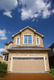 New cottage with garage in front of it. New two-storied beige stone cottage with garage in front of it Royalty Free Stock Photo