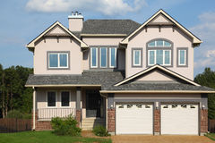 New cottage with two garages. New two-storied pink brick cottage with two white garages and brown roof Royalty Free Stock Image