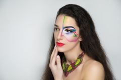 Fantasy woman make up. New creative make-up, conceptual idea for ethnic party. Brunette. Red blue green color graphic shapes, cosmetics shadows paints lines Royalty Free Stock Photography