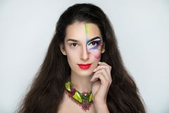Fantasy woman make up. New creative make-up, conceptual idea for ethnic party. Brunette. Red blue green color graphic shapes, cosmetics shadows paints lines Stock Images