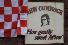 New Cumnock sign decorated with a flag. New Cumnock sign decorated in support of New Cumnock`s Glenafton football team in advance of the Scottish junior cup stock image