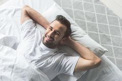 Cheerful guy waking up in the morning. New day, new emotions. Top view portrait of happy young man awakes on soft bed and smiling Royalty Free Stock Photography
