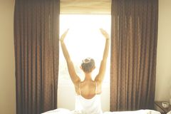 Big spacey hotel room full of sunlight and sun beams. Optimistic start of the day. Blond woman cozy home clothing welcoming the mo. New day new life concept Royalty Free Stock Photo