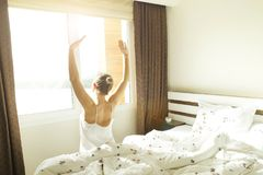 Big spacey hotel room full of sunlight and sun beams. Optimistic start of the day. Blond woman cozy home clothing welcoming the mo. New day new life concept Stock Photos