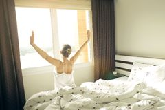 Big spacey hotel room full of sunlight and sun beams. Optimistic start of the day. Blond woman cozy home clothing welcoming the mo. New day new life concept Stock Image