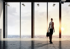 New day new opportunities. Back view of businesswoman in modern office facing sunrise Stock Photo