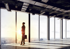 New day new opportunities. Back view of businesswoman in modern office facing sunrise Royalty Free Stock Photo